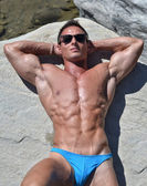 Fit and athletic young bodybuilder resting and sunbathing on rock — Stock Photo