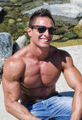 Attractive young muscle man smiling, sitting on a rock — Stock Photo