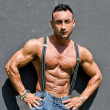 Foto Stock: Muscle man with jeans and suspenders on grey wall