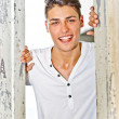Happy, smiling young man in white between wooden doors — Stock Photo