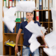 Постер, плакат: Young man in very messy office with documents flying