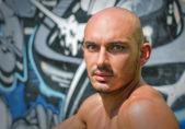 Headshot of bald young man shirtless outdoors — Stock Photo