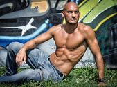 Bald young man shirtless outdoors sitting — Stock Photo