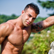 Attractive young bodybuilder outdoors — Stockfoto