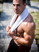 Very muscular man outdoors with towel around his neck — Stock Photo