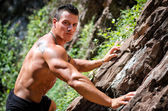 Handsome, muscular, shirless climber climbing rock wall — Stock Photo