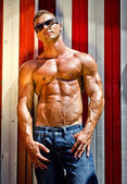Handsome and muscular muscle man against beach changing room wall — Stock Photo