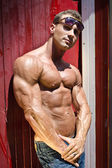 Handsome and muscular male bodybuilder against beach changing room — Stock Photo