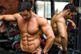 Muskulös manliga kroppsbyggare vilar i gymmet under träning — Stockfoto