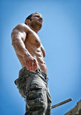 Hot, muscular construction worker shirtless seen from below — Stock Photo
