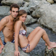 Romantic young couple in swimming suit on rocks — Stock Photo