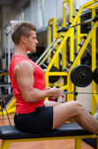Attractive young man working out on gym equipment — Stock Photo