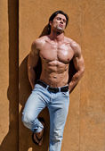 Handsome young man shirtless with jeans against a wall, eyes closed — Stock Photo