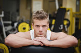 Attractive young athletic man resting on gym equipment — Stock Photo