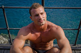 Handsome young muscle man sitting with sea behind — Stock Photo
