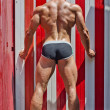 Attractive young man outdoors, seen from the back, with muscular body, legs and buttocks — Stock Photo