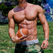 Close-up of torso of very muscular man naked with football — Stock Photo