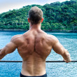 Muscular young man's back. Leaning on metal railing — Stock Photo