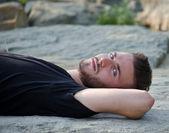 魅力的な若い男は岩の上に彼の背中に横になっているカメラで — ストック写真