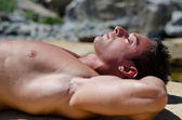 Handsome young man laying naked on white rocks, eyes closed — Stock Photo
