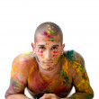 Stock Photo: Handsome young mwith skin all painted with Honi colors, resting on his elbows