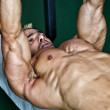 Muscular man working out in the gym on bench — Stock Photo