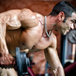 Muscular male bodybuilder working out in gym, exercising triceps — Stock Photo