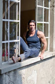 Attractive, muscular man sitting on open window — Stock Photo