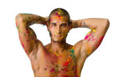 Attractive young man shirtless, skin painted all over with bright colors — Stock Photo
