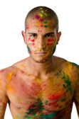 Attractive young man shirtless, skin painted all over with bright Honi colors — Stock Photo