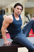 Handsome, muscular man sitting on desk, with jeans and tanktop — Stock Photo