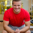 Attractive young man in gym sitting on bench, smiling — Stock Photo