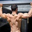Muscular back of male bodybuilder hanging from metal structure — Stock Photo
