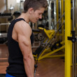 Foto Stock: Teen bodybuilder exercising triceps with gym equipment
