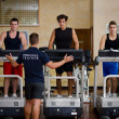 Stock Photo: Three young men exercising on treadmills with personal trainer