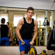 Stock Photo: Teen bodybuilder exercising pecs muscles with gym equipment