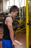 Teen bodybuilder exercising triceps with gym equipment — Stock Photo