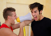 Personal trainer motivating client yelling with megaphone — Stock Photo