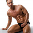 Attractive young muscular man posing on his knees — Stock Photo