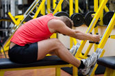Handsome young man working out on gym equipment — Stock Photo