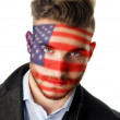 Handsome young man with face painted with American flag — Stock Photo