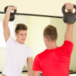 Two young men in gym working out with kettlebells — Stock Photo #34656207