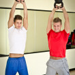 Two young men in gym working out with kettlebells — Stock Photo #34656255