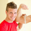 Personal trainer measuring client bicep with tape meter — Stock Photo