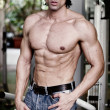 Handsome muscular man in jeans shirtless looking away — Stock Photo