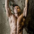 Attractive muscleman against rough wall, arms over his head — Stock Photo #34656711