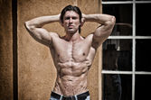 Muscular young bodybuilder shirtless outdoors in jeans — Stock Photo