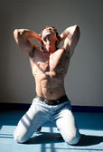 Attractive muscleman kneeling shirtless with hands behind head, looking up — Stock Photo