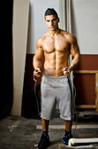 Athletic, muscular young man shirtless with jumping rope — Stock Photo