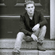 Attractive blue eyed, blond young man sitting on stair steps — Стоковая фотография